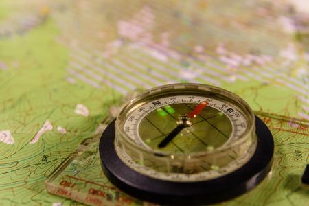 Touristic magnetic compass lying on topographical map Stock Photo
