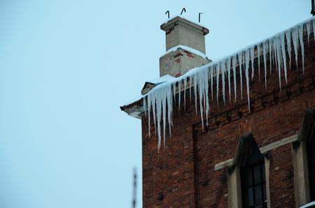 Icicles hanging from the roof of the old building