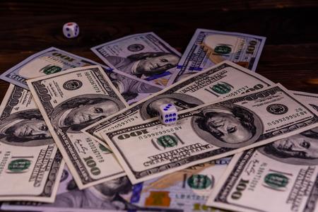 Dice in flight above the one hundred dollar bills. Gamble concept Foto de archivo