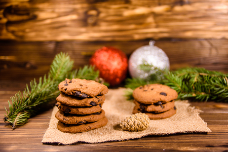 Chocolate chip cookies and christmas decorations on wooden table