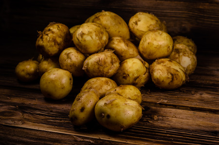 Pile of young potato on rustic wooden table