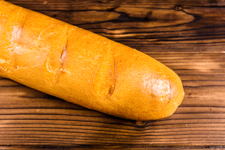 French white baguette on rustic wooden table. Top view Stock Photo