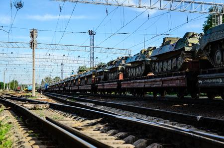 Tren de carga que transporta tanques en una plataforma de carga