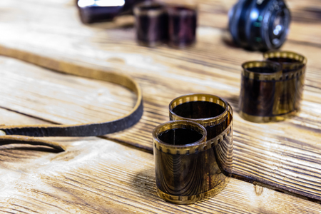 Old lens and films on rustic wooden table