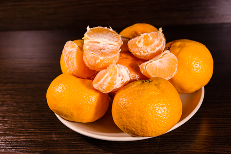 Plate with mandarins on dark wooden table