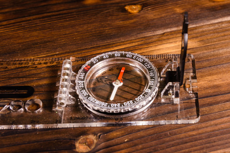 Touristic magnetic compass on a rustic wooden table Stock Photo