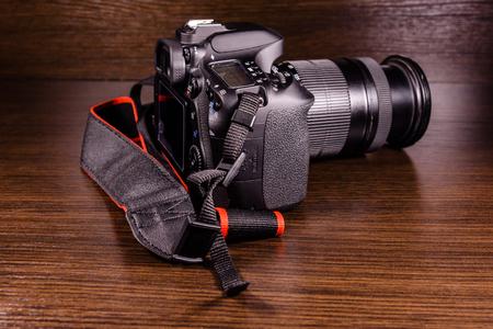 Modern dslr camera on a dark wooden table Stock Photo