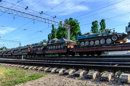 Cargo train carrying tanks on a freight platform Stock Photo