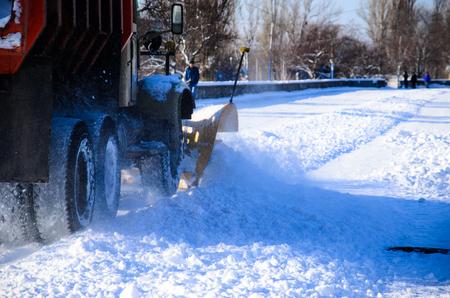 Snow plow truck workiyng in a city park. Kremenchug, Ukraine
