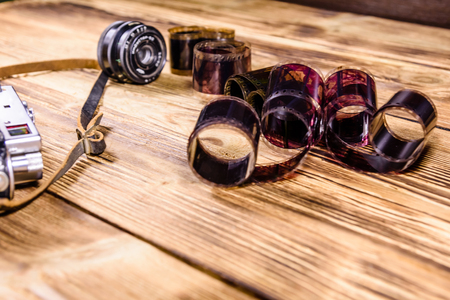 Old rangefinder camera and films on rustic wooden table