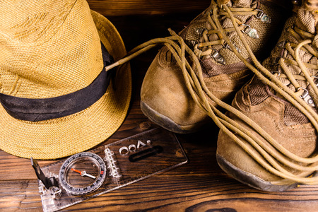 Touristic magnetic compass, boots and hat on a rustic wooden table Banque d'images