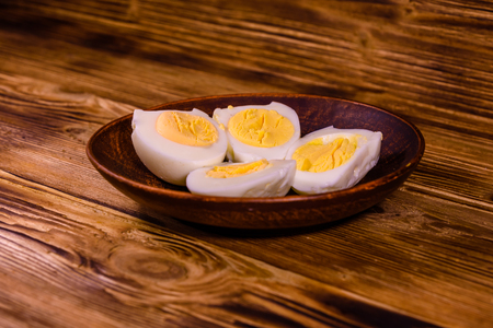 Ceramic plate with peeled boiled eggs on  rustic wooden table