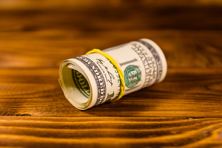 Roll of one hundred dollar bills with rubber on rustic wooden table 写真素材