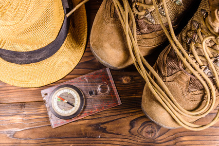 Touristic magnetic compass, boots and hat on a rustic wooden table. Top view