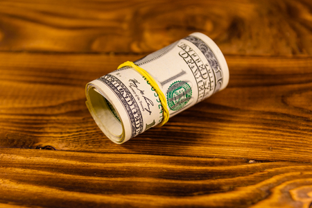 Roll of one hundred dollar bills with rubber on rustic wooden table Stock Photo
