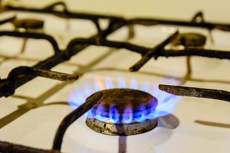 Gas burner on a white kitchen stove