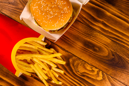 French fries and hamburger on rustic wooden table. Top view