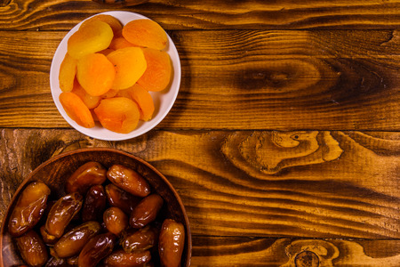 Date fruits and dried apricots on rustic wooden table. Top view Stock Photo