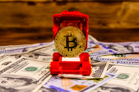 Golden bitcoin in car-shaped gift box for jewelry on one hundred dollar bills