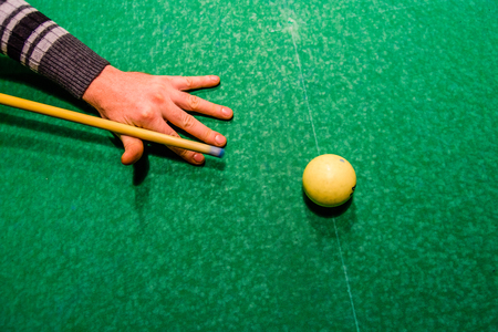 Player arm with the cue and ball on a green cloth. Russian billiard. Top view