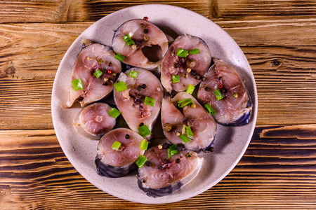 Sliced scomber fish with green onion on a ceramic plate on rustic wooden table. Top view