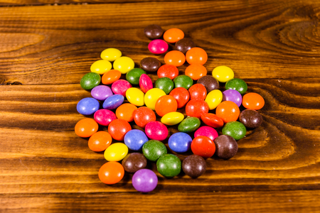 Pile of multicolored candies on a wooden table 免版税图像