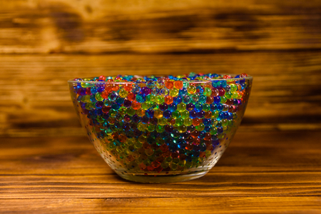 Multicolored hydrogel balls in glass bowl on wooden table