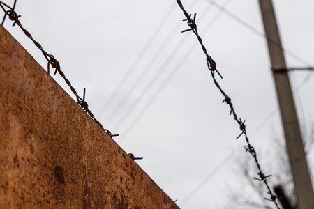 Barbed wire against sky on cloudy day