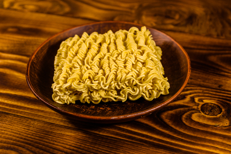 Ceramic plate with instant noodles on rustic wooden table Stock Photo