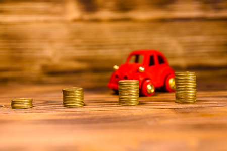 Stacks of the coins and red toy car on rustic wooden table