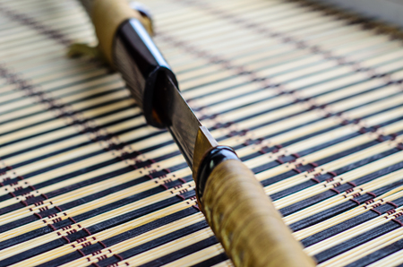 Japanese sword katana on a bamboo mat. Selective focus