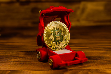 Golden bitcoin in car-shaped gift box for jewelry on wooden table