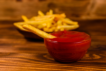 Fresh french fry dipped into tomato sauce