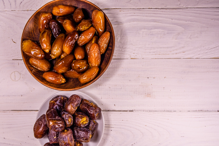 Date fruits on a white wooden table. Top view