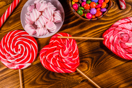 Ceramic plate with marshmallow, candy cane and lollipops on rustic wooden table. Top view