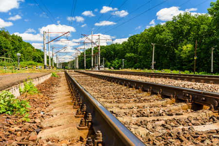 View on a railroad track and white clouds in a blue sky Standard-Bild