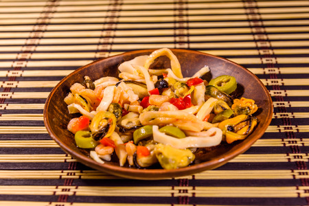 Ceramic plate with different sea food and olives on bamboo mat 版權商用圖片