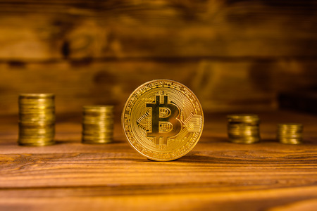 Bitcoin and stack of coins on rustic wooden table Stock Photo
