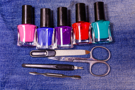 Different manicure tools and nail polishes on blue jeans. Top view Stock Photo