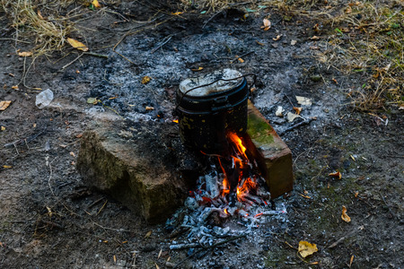 Cooking food in a kettle on bonfire in forest