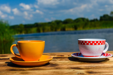 Two cups of coffee on rustic wooden table at the riverside