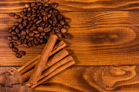 Pile of the coffee beans and cinnamon sticks on rustic wooden table. Top view Фото со стока