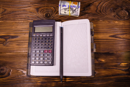 Opened notepad, one hundred dollar banknotes, scientific calculator and pencil on rustic wooden table. Top view