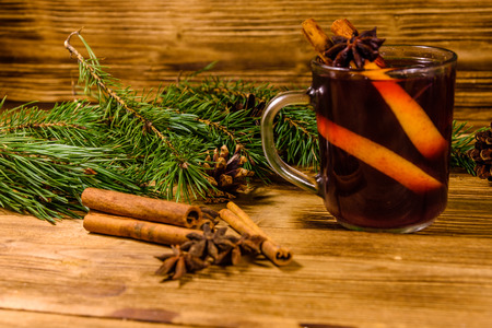 Cup of mulled wine with cinnamon and fir tree branches on rustic wooden table