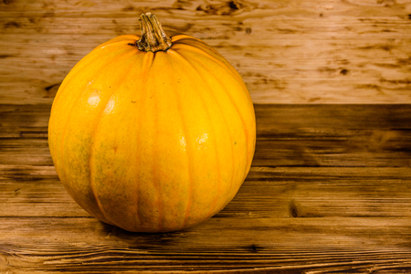 Ripe orange pumpkin on rustic wooden table