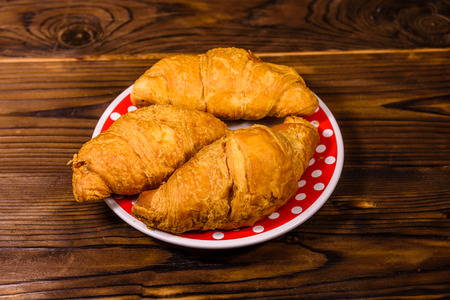 Plate with croissants on rustic wooden table Фото со стока