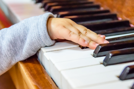 Child hand on a shiny piano keys