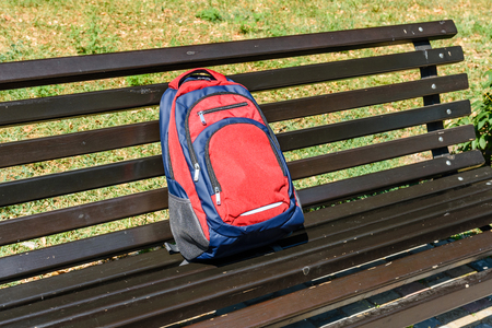 Tourist backpack on bench in city park Imagens