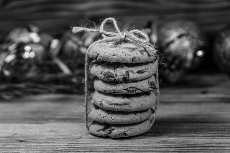 Stack of chocolate chip cookies on sackcloth in front of christmas decorations. Black and white