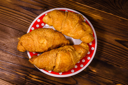 Plate with croissants on rustic wooden table. Top view